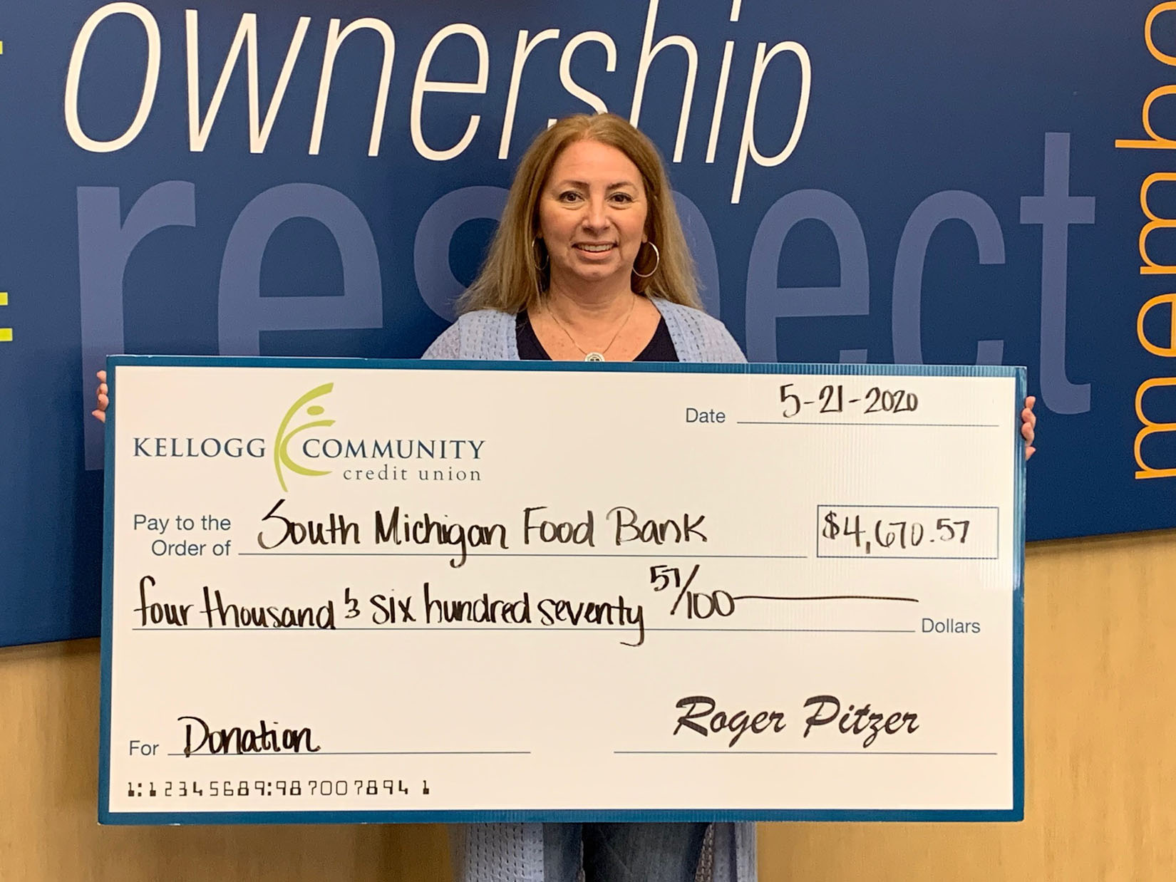 Tracy Miller hold South Michigan Food Bank Check